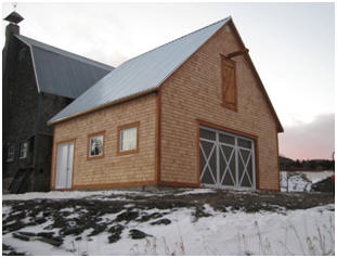 This new, cedar-sided barn in Quebec will weather to a dark gray and match the old the farm barn behind it. It was built from inexpensive, stock pole-barn plans by architect Don Berg at BarnsBarnsBarns.com