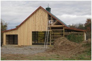 There's no law that says that a pole barn has to look like a box. Imagine this Walnut Barn when it is finished with a loft hatch and big barn doors. It's being built from inexpensive plans by architect Don Berg, available at BackroadHome.net